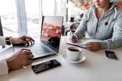 Entretiens de jeune femme à son patron et notes de prises dans un bloc-notes Deux personnes s'asseyent dans un café à la table bl images stock