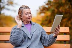 Entretiens de ondulation d'une femme mûre avec quelqu'un sur le comprimé au parc d'automne Extérieur en parc d'automne Photo libre de droits