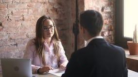 Entrevista amistosa joven de la tenencia del encargado de la hora con el candidato en oficina almacen de metraje de vídeo