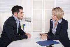 Entrevista con el encargado y el hombre atractivo joven en la oficina. Imagenes de archivo