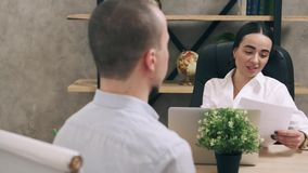 Entrevista de trabajo joven de la tenencia de la mujer de negocios con el posible empleado