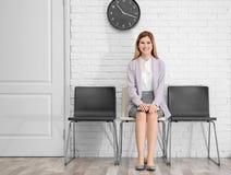 Entrevista de trabalho de espera da jovem mulher imagem de stock
