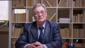Entrevista del hombre de negocios mayor que habla en c?mara en fondo de los estantes de librer?a almacen de video