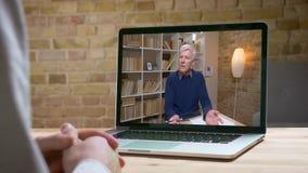 Entrevista en línea con el experto mayor con el lápiz y el cuaderno que habla seriamente con su socio detrás de la pantalla almacen de video