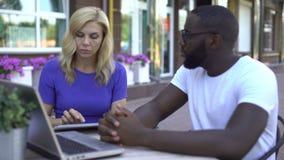 Entrevista que conduce con el candidato masculino en café, comunicación del patrón de sexo femenino almacen de video