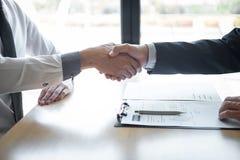 Entrevue d'emploi r?ussie, employeur de patron dans le costume et nouvel employ? se serrant la main apr?s n?gociation et entrevue images stock