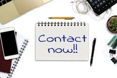 Entrez en contact maintenant sur le bloc-notes - bureau blanc avec le smartphone avec Image libre de droits