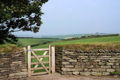 Entry. Into a field through gate in a traditional dry-stone wall royalty free stock photo