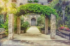 Entry arch covered climbing plants. Entry arch on four columns covered by climbing plants is located in front of stone house. On either side of the wide pavement Royalty Free Stock Photo