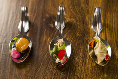 Entry, entree and dessert of finger food in a spoon. Royalty Free Stock Photos