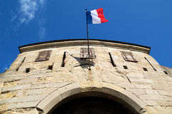 Entry with flag. Entry to the Castle of the Cite of Carcassonne with the French flag undulating on blue sky royalty free stock image