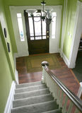 Entry hall stairs and front door. Laminate floors and white molding Royalty Free Stock Image