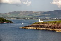 Dingle bay and harbour. Entry point of Dingle harbour, co Kerry, Ireland, with lighthouse and cruising ships leaving the harbour Stock Photo