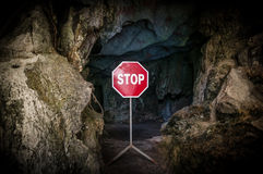 Entry to dark cave blocked with STOP sign. Stock Image
