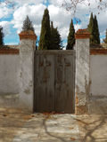 Entry to heaven. Closed door at cementery entry. Place were dead people is buried. Cypress. Blue and cloudy sky royalty free stock photo