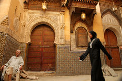 Entry to the mosque. Muslim woman dressed in black walking in front of the mosque in the medina in Fes, Morocco Stock Photo