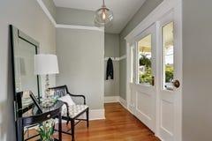 Entryway med den gråa väggar, konsoltabellen och trägolv Arkivfoton