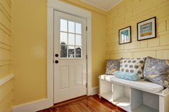 Entryway with yellow walls and storage bench in white Stock Photo