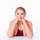 Entschiedene blonde Frau, die im spärlichen Bürolächeln sitzt Stockfotografie