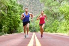 Entschlossene Athleten, die auf Straße gegen Bäume laufen lizenzfreies stockfoto