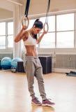 Entschlossene Frau, die mit gymnastischen Ringen in der Turnhalle trainiert Stockfotos