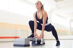 Entschlossene Frau, die Stepp-Aerobic mit Handgewichten ausübt Stockbild