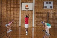 Entschlossene Highschool Kinder, die Basketball spielen Stockbilder