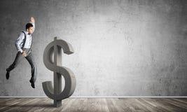 Entschlossener Bankermann im leeren konkreten Raum, der Dollarzahl bricht Stockfotos