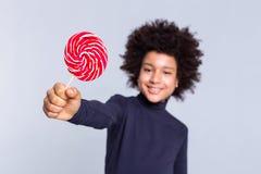 Entschlossener dunkelhaariger froher Junge, der Hand mit Süßigkeit in ihr auszieht lizenzfreies stockbild