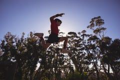 Entschlossener Junge, der über Hindernis springt stockfotografie