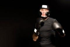 Entschlossener junger Boxer mit seinen Fäusten am bereiten stockfotografie