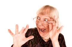 Entsetzte ältere Frau, die über der Oberseite ihres g schaut Lizenzfreie Stockbilder