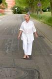 Entsetzte ältere Frau, die an der Straße allein geht Lizenzfreies Stockfoto