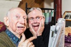 Entsetzte ältere Paare mit Zeitung stockbild