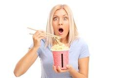 Entsetzte blonde Frau, die chinesische Nudeln isst Stockfoto