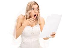 Entsetzte Braut, die eine Rechnung betrachtet Stockbild