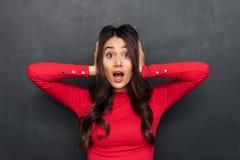 Entsetzte Brunettefrau in der roten Bluse, die ihre Ohren bedeckt stockfotos
