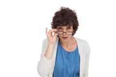 Entsetzte Frau, die über ihren Gläsern schaut Lizenzfreie Stockbilder