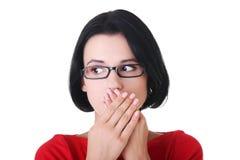 Entsetzte Frau, die ihren Mund mit den Händen abdeckt Stockbilder