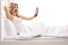 Entsetzte Frau, die im Bett liegt und einen Spiegel betrachtet Stockbilder