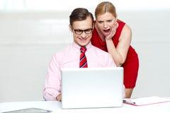 Entsetzte Frau, die Laptop untersucht. Mannfunktion lizenzfreie stockbilder
