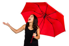 Entsetzte Frau, die oben beim Halten des roten Regenschirmes schaut Lizenzfreies Stockfoto