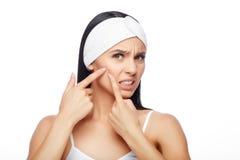 Entsetzte Frau, die Pickel auf Stirn betrachtet stockbild