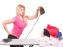 Entsetzte Frau, die ungefähr Eisen hält, um das Bügeln zu tun stockbild