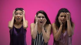 Entsetzte gemischtrassige Freundinnen, die schreckliche Fernsehshow, negative Gefühle aufpassen stock footage
