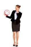 Entsetzte Geschäftsfrau, die Bürouhr hält Stockfotos