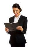 Entsetzte Geschäftsfrau, die ihre Anmerkungen liest Lizenzfreies Stockbild
