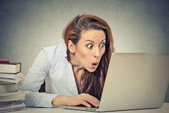 Entsetzte Geschäftsfrau, die vor Laptop-Computer sitzt Stockbild