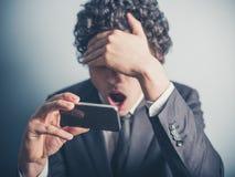 Entsetzte Geschäftsmannlesung auf seinem Smartphone Stockbilder