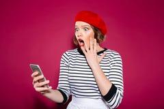 Entsetzte Ingwerfrau, die Backe bei der Anwendung von Smartphone hält stockbild